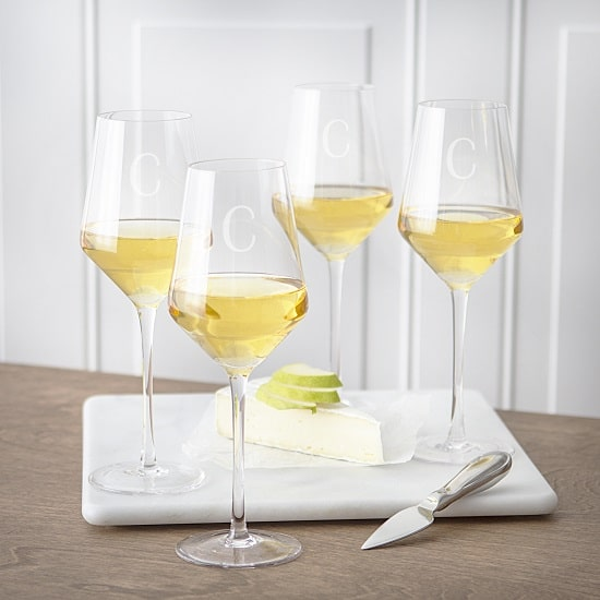 Four white wine glasses filled with Chardonnay