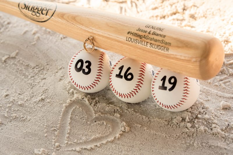 A custom Louisville Slugger bat being used as a save the date for a beach wedding.