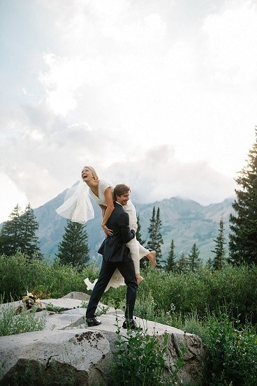 groom-holding-bride-top-of-mountain