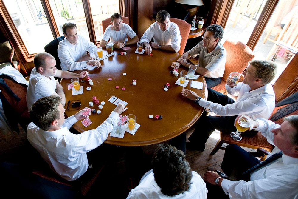 The groom plays poker with his groomsmen prior to the start of his wedding