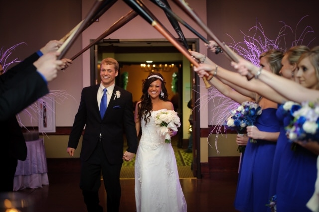 enter the wedding reception under a canopy of baseball bats