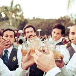 manly wedding ideas featuring groomsmen drinking whiskey and smoking cigars