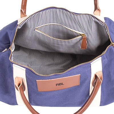 The spacious interior of the personalized blue duffle bag features a zipper  pocket and plenty of 1c2ed38a94