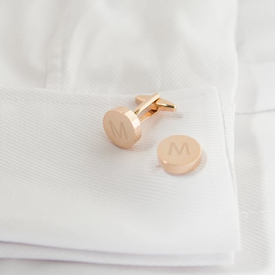 "Rose gold cufflinks with the letter ""M"" looking swell against a white button-up dress shirt."