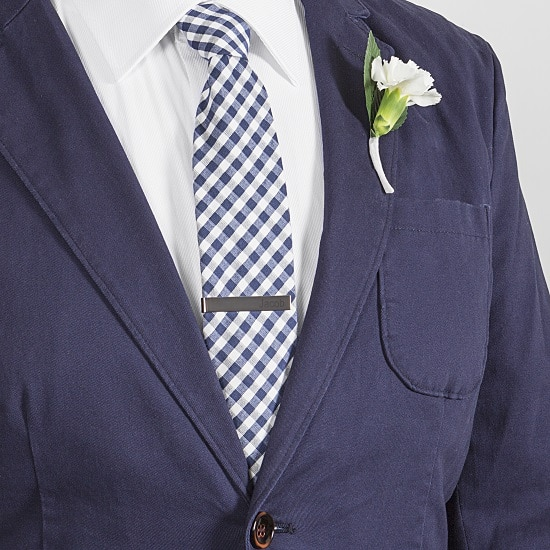 Groom in a blue suit with custom gunmetal tie clip