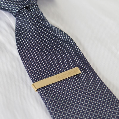 "Engrave a name, set of initials or ""groomsmen"" on the front of the gold tie clip."