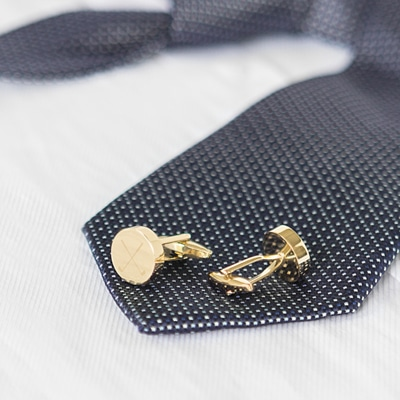Closeup of Gold Round Cufflinks With Golf Club Design Shown With Dark Spotted Tie