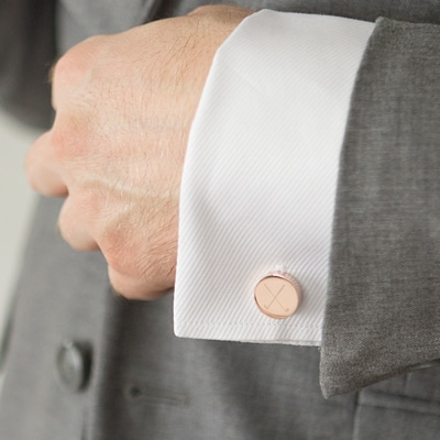 Gold round cufflinks with golf club design on white shirt and grey sport coat