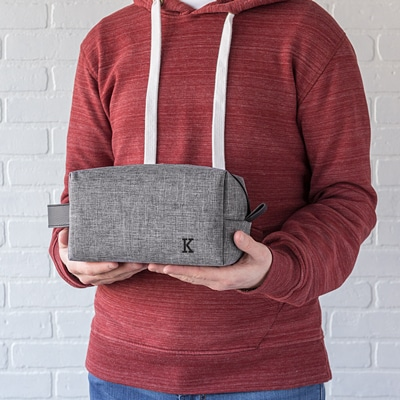 Add up to three initials to be embroidered on the front of the grey dopp kit