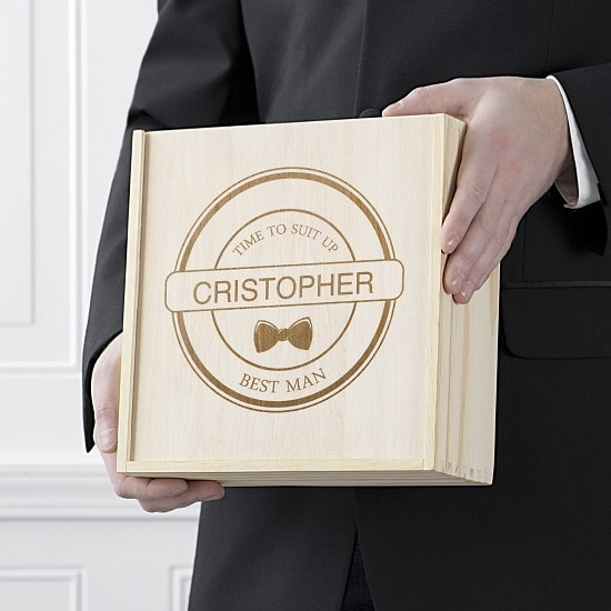 A proud best man holds his customized wooden gift box