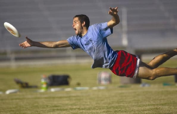 ultimate frisbee player diving for frisbee