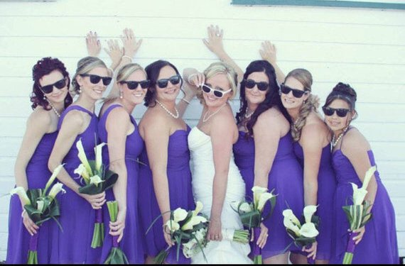 Bridesmaids in purple dresses looking awesome in our matching black sunglasses.