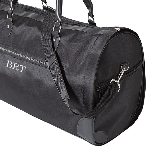 The sleek black garment bag boasts an adjustable shoulder strap for easy travel.