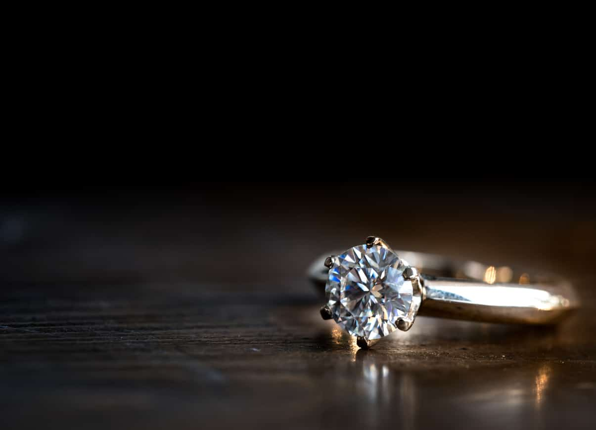 golden diamond ring on the wooden table