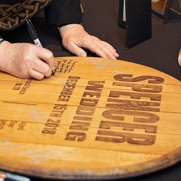 A wedding guest signing the Knob Creek wedding barrel.