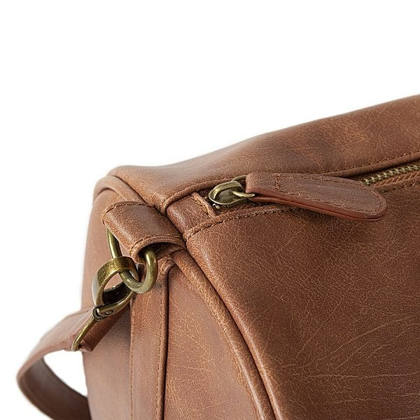 The Vegan Leather duffle bag features antique golden zippers.