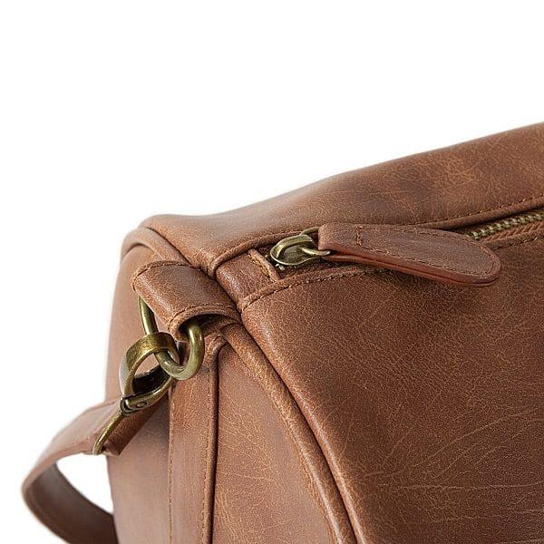 The Vegan Leather duffle bag features antique golden zippers.