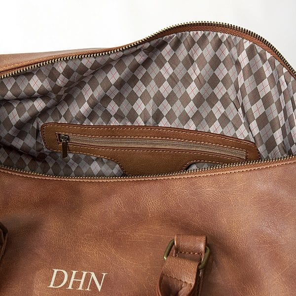 The interior of the Vegan Leather Duffle Bag features a handsome argyle patterned lining.