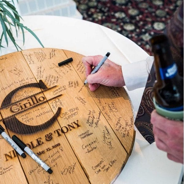 A wedding guest signs his signature on the Big Letter Whiskey Barrel.
