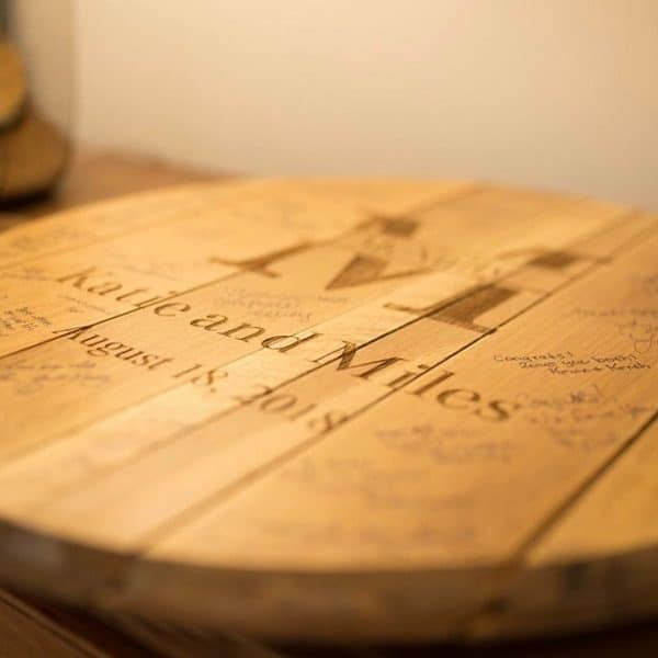 A beautiful whiskey barrel guest book displayed at a wedding reception.