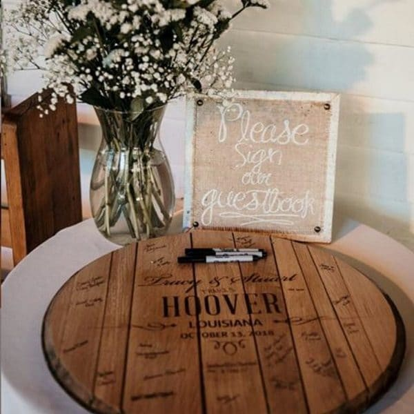 Guests checking in and signing a whiskey barrel guest book
