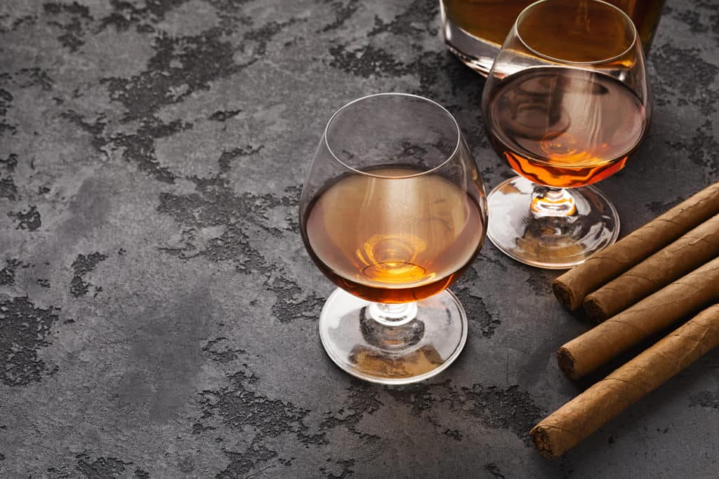 Luxury lifestyle attributes of groomsmen. Two glasses with cognac and cigars on marble table, copy space