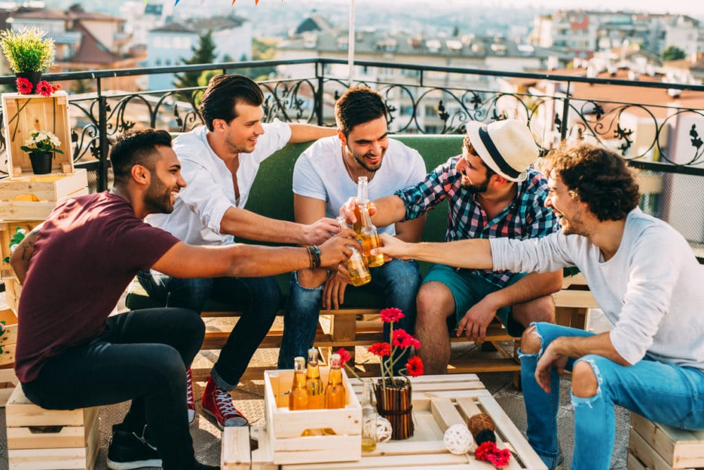 five groomsmen toasting at a party on the roof.