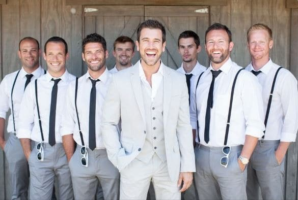 groomsmen wearing matching suspenders behind the groom who is front and center