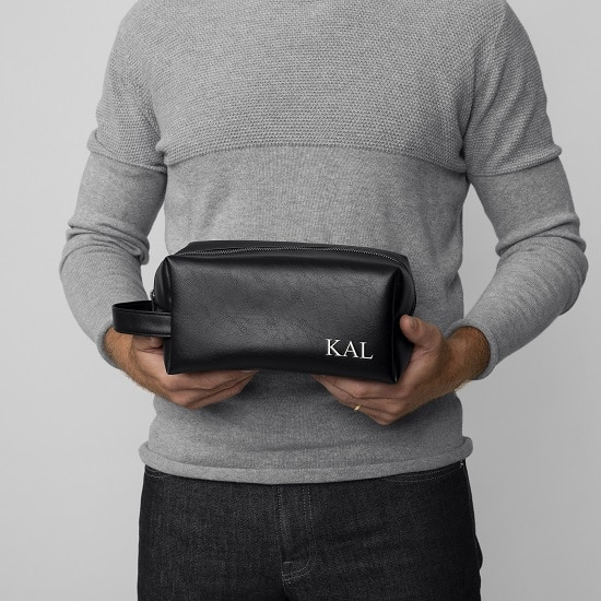 A handsome groomsman holding the 5102BK Men's Dopp Kit
