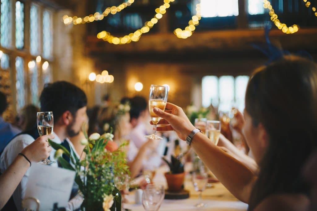 raising glasses at wedding rehearsal dinner